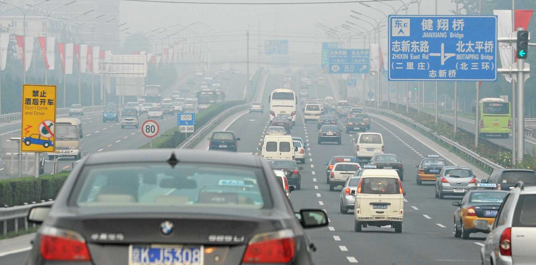 Highrise buildings are barely visible as is the road ahead on a busy freeway in Beijing.