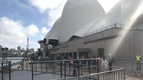 The first locals have started filing through security and lining the metal barricades at the base of the Opera House.