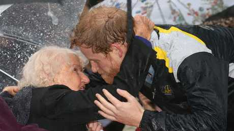 Prince Harry didn't let the rain stop having a second smooch with Daphne Dunne when he met her again in 2017. Picture: Toby Zerna