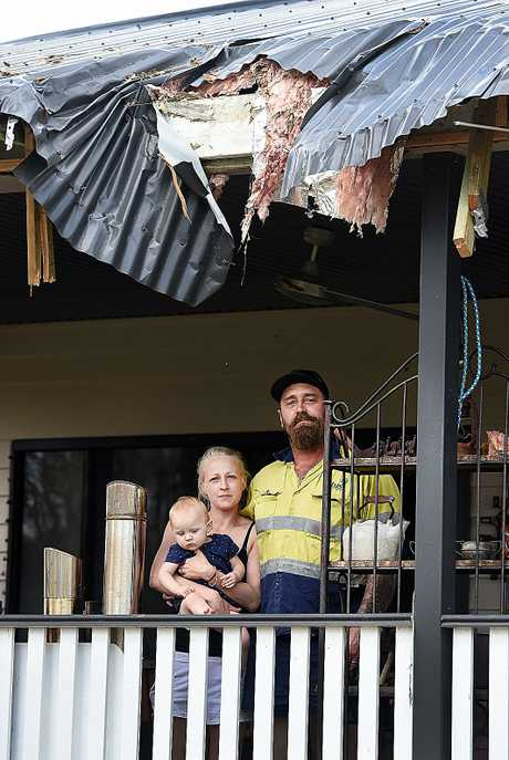 Jeremiah Knight, wife Kimberley and one-year-old daughter Willow with damage to the back of their house.