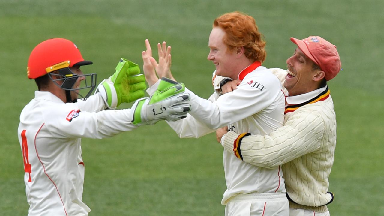 Lloyd Pope celebrates with Redbacks teammates after taking his maiden Sheffield Shield wicket. (Picture: AAP Image/David Mariuz)