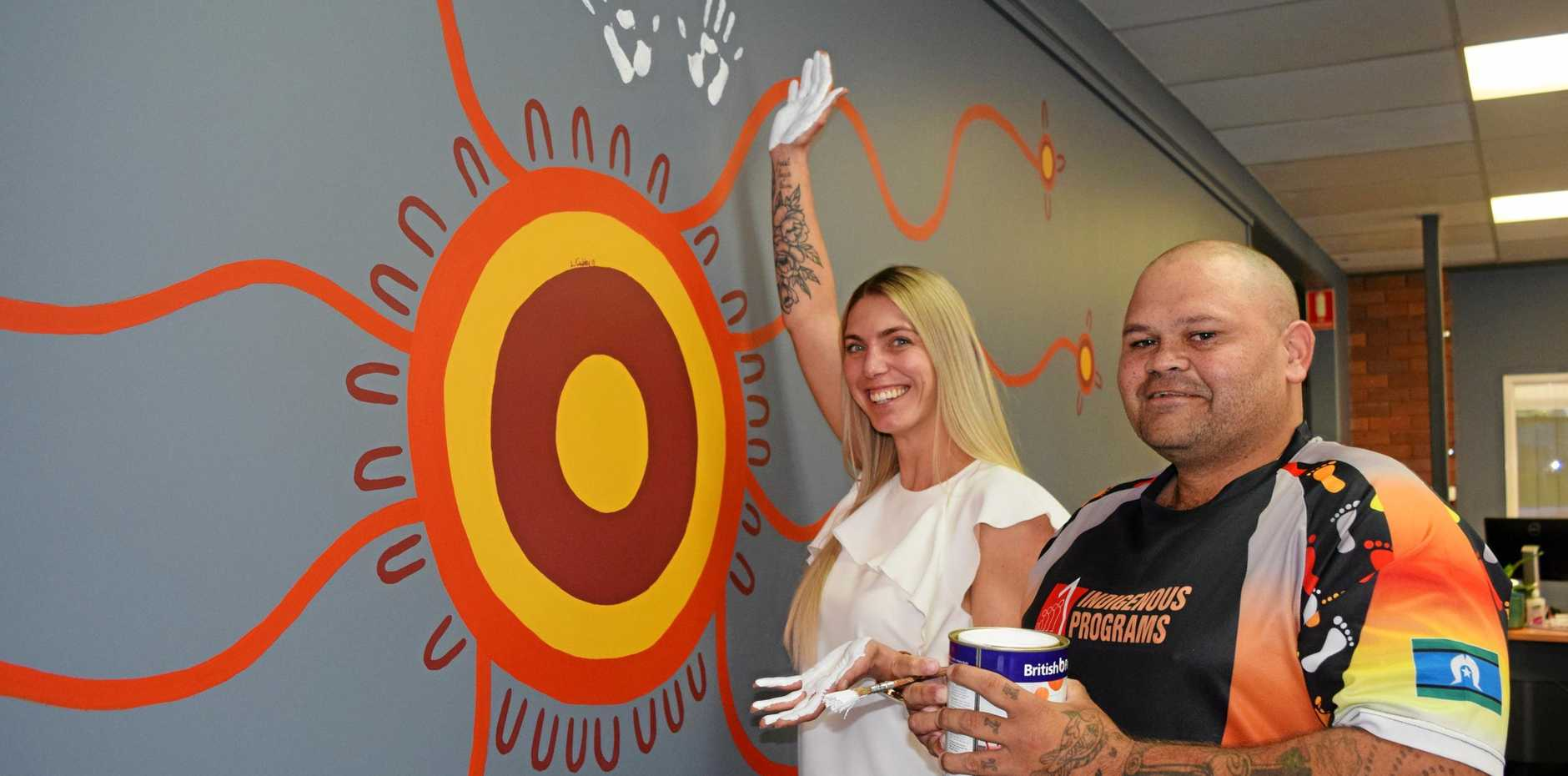 PAYING RESPECT: Sarah Peterson and artist Lionel Cubby at BEST employment in front of their new mural.
