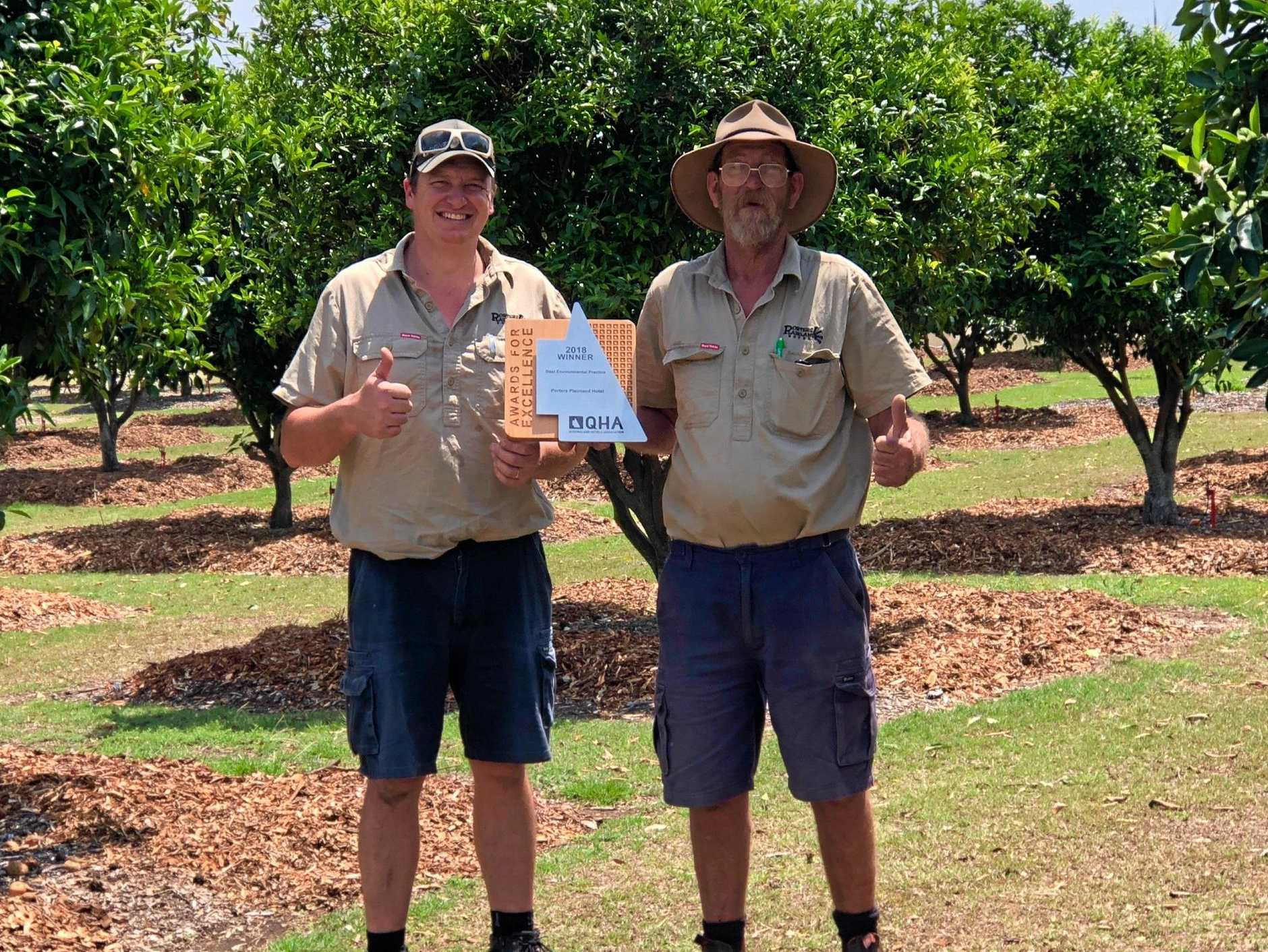 SUCCESS: Tony Gratton and Craig Hutchence holding an award for the Plainland Porters Hotel's green policy.
