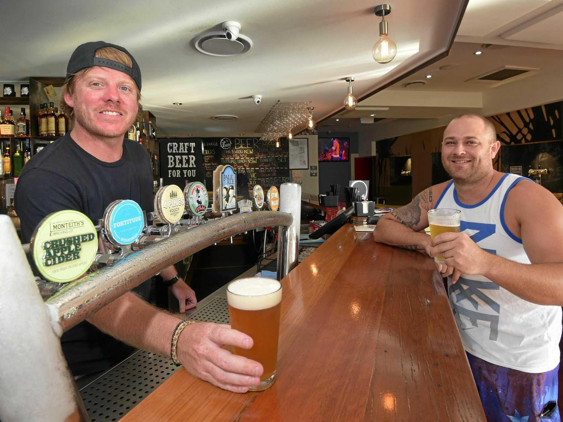Owner of Taps Mooloolaba, Steve Barber, serves up a craft beer to Daniel Bennett.