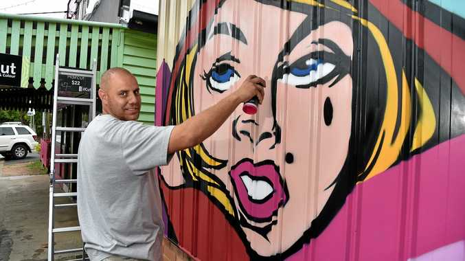 Artist Daniel Krause creating his mural on the side of the Bloomhill op shop in the lead up to Nambour Street Art Festival.