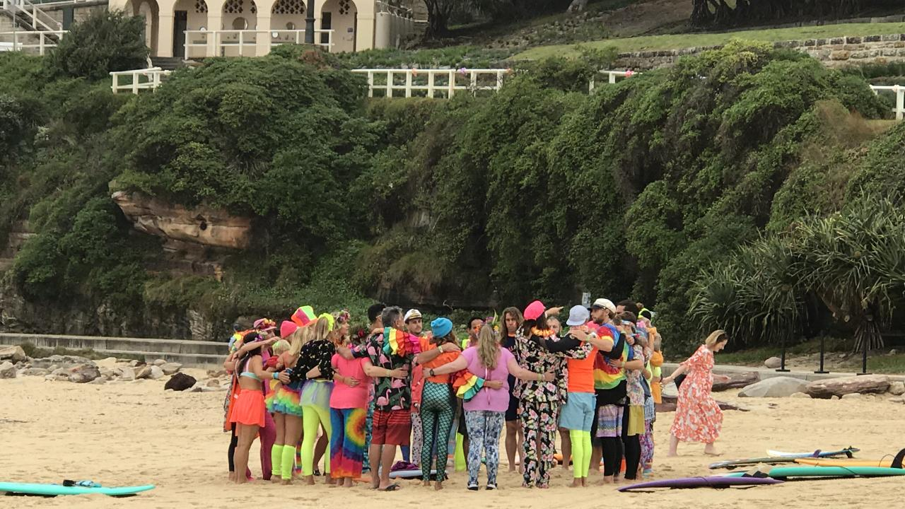 Members of Bondi's One Wave group, the surfing community's mental health and wellbeing awareness group, arrive on Bondi Beach to take part in Fluro Friday where they will share their experiences with mental health issues while surfing and doing yoga.