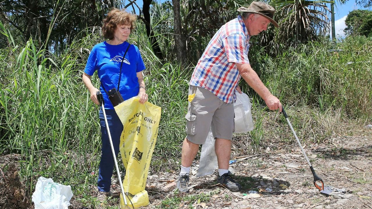 Volunteers Odette Aspinall and Andrew Smart clean up rubbish at Chinaman Creek, Ray Jones Drive. PICTURE: JUSTIN BRIERTY