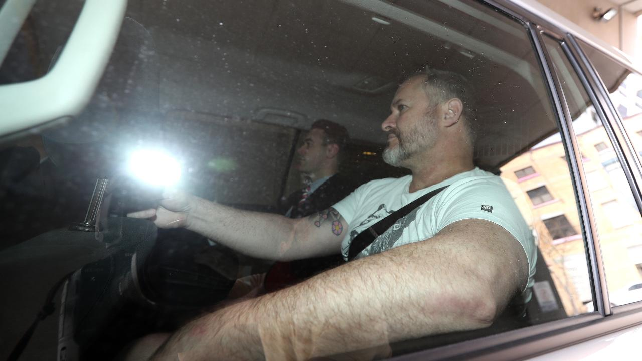 Lawyer Adam Magill being driven into the Brisbane Watchhouse after his arrest on fraud charges.