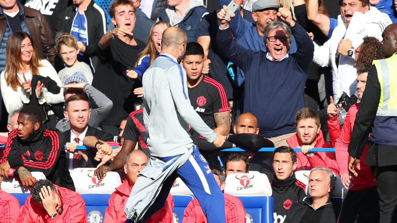 A member of the backroom staff at Chelsea celebrates his sides second goal infront of Jose Mourinho