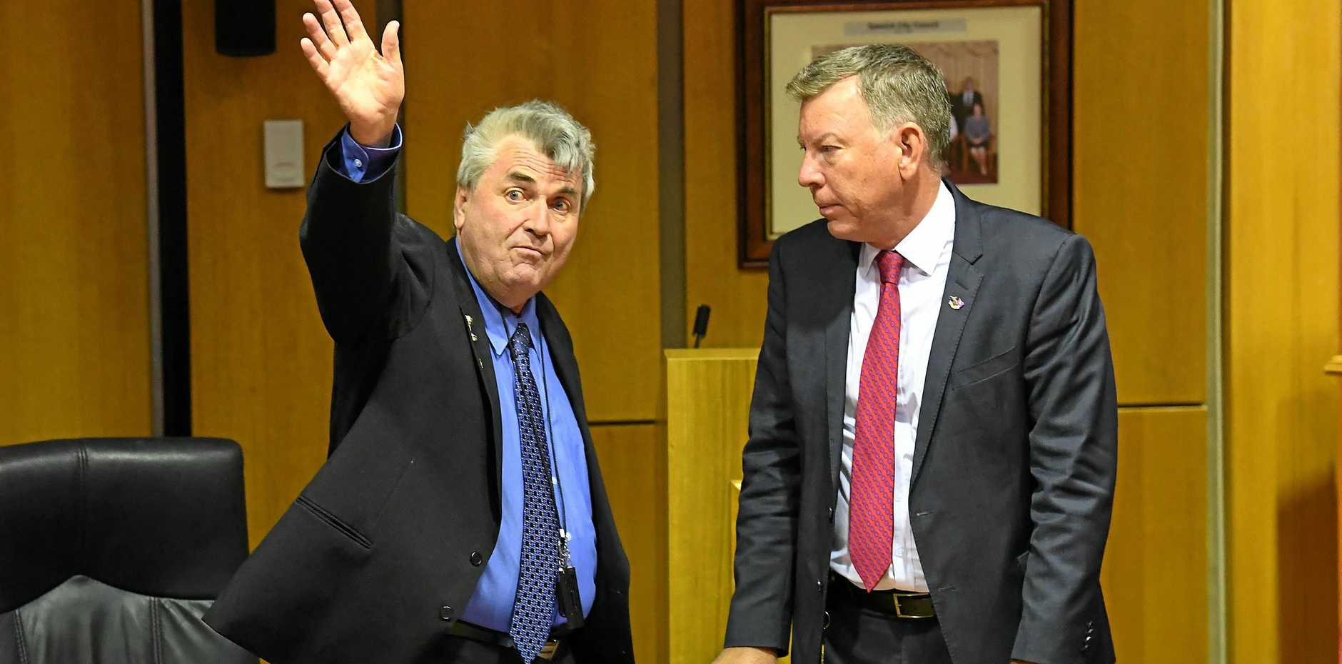 Cr David Pahlke waves goodbye as acting Mayor Wayne Wendt (right) looks on following the Ipswich City Council's final meeting at the Ipswich City Council Chambers in August.