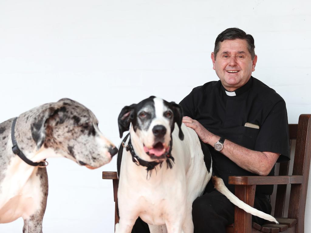 Father Chris Riley with his dogs. He is devastated that two schools may now not be possible in severely disadvantaged areas. Picture: Brett Costello