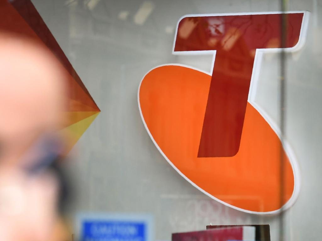 People walk past a sign of telecommunications company Telstra in Melbourne. Picture: AFP