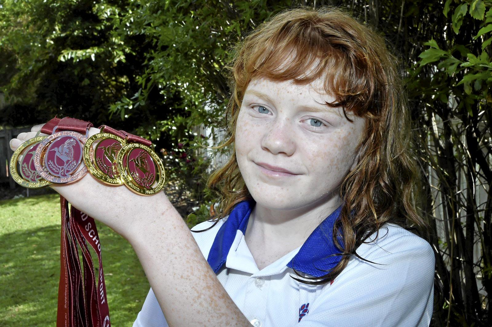 ATHLETIC STAR: Megan Seipel, 11, proudly shows off the medals she won at last weekend's 10-12 years Track and Field State Championships in Cairns.