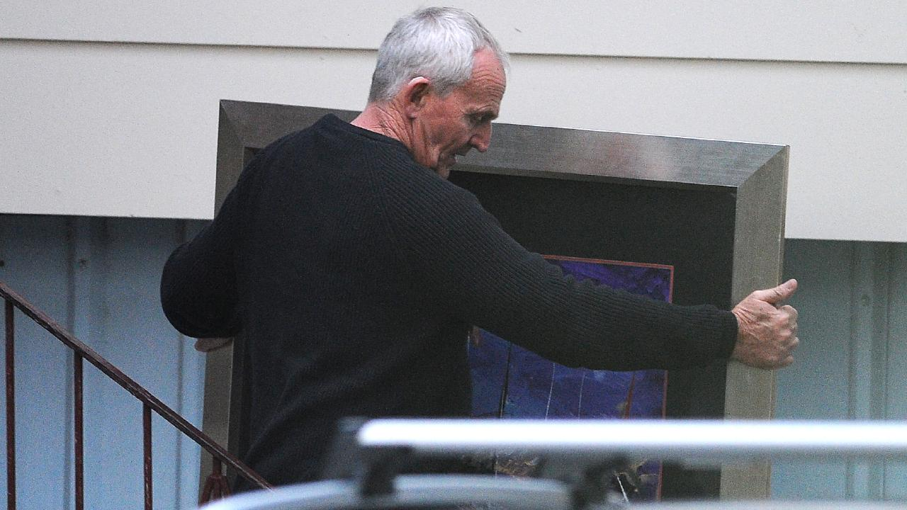 Logan councillor Russell Lutton removes a painting from a house in June.