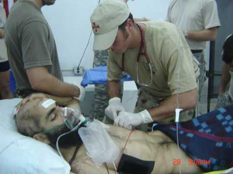 Medic Brad Watts works on a wounded patient in the field hospital at Tarin Kowt