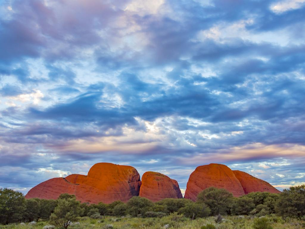 Sunset with dramatic clouds over the domes of Kata Tjuta rocks in the Australian desert.