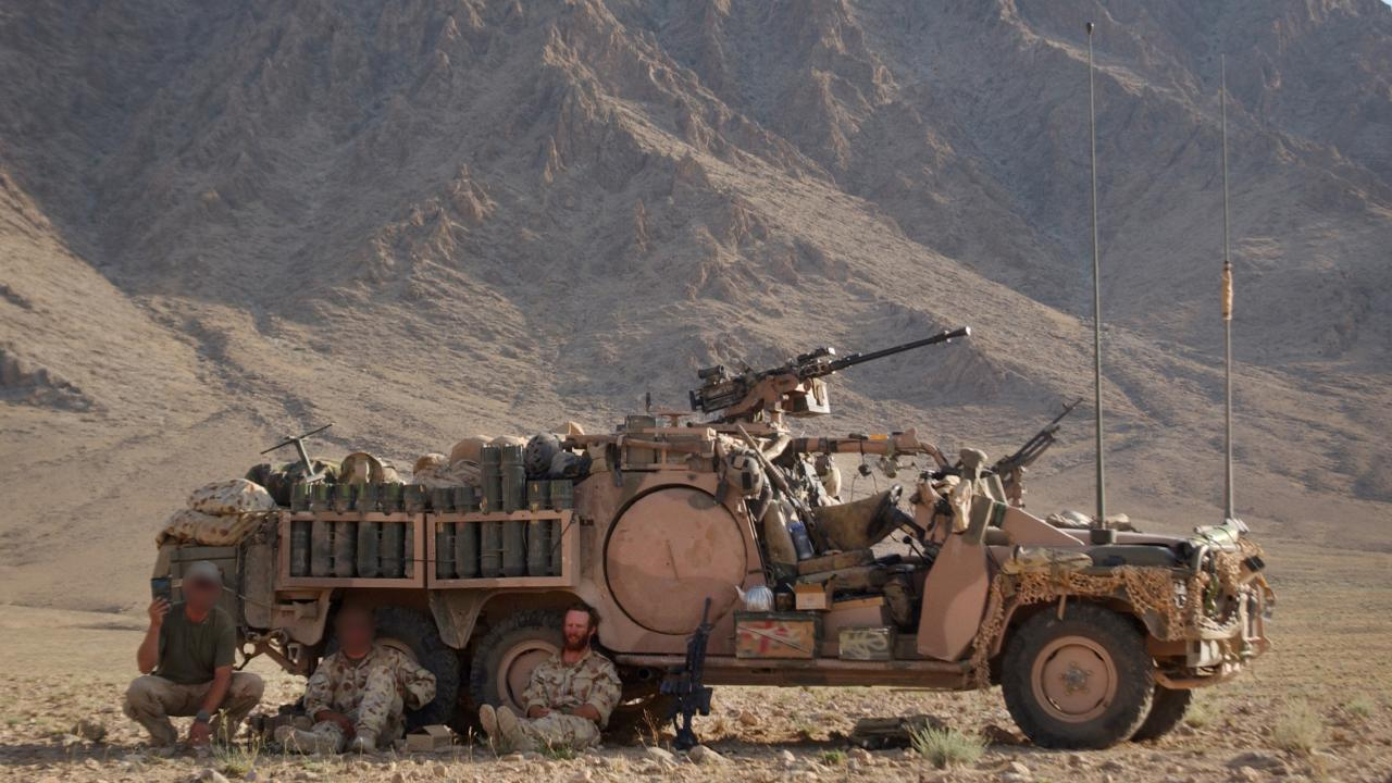 Australian special forces get some respite in the shade of the Long Range Patrol Vehicle near Chora in Afghanistan.