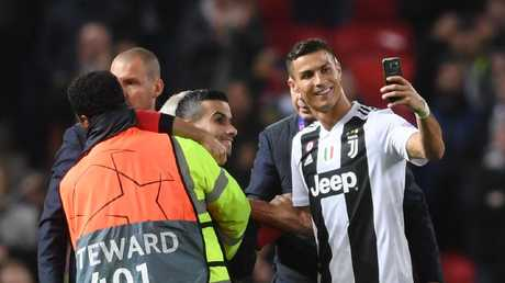 Cristiano Ronaldo of Juventus takes a selfie with a pitch invader