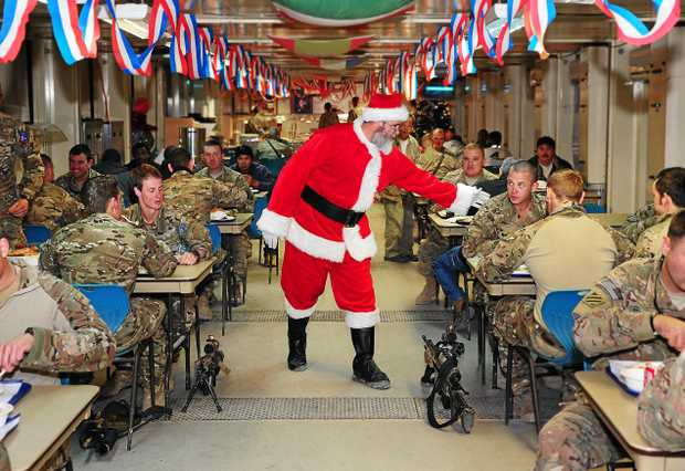 CHEERFUL: US Contractor Mr Troy Petteway got into the Christmas spirit at Multi National Base - Tarin Kot, dressing up as Santas Claus, helping to hand out Christmas care packages from Australia and passing on holiday greetings to soldiers, sailors and airmen deployed to Uruzgan province, Afghanistan.