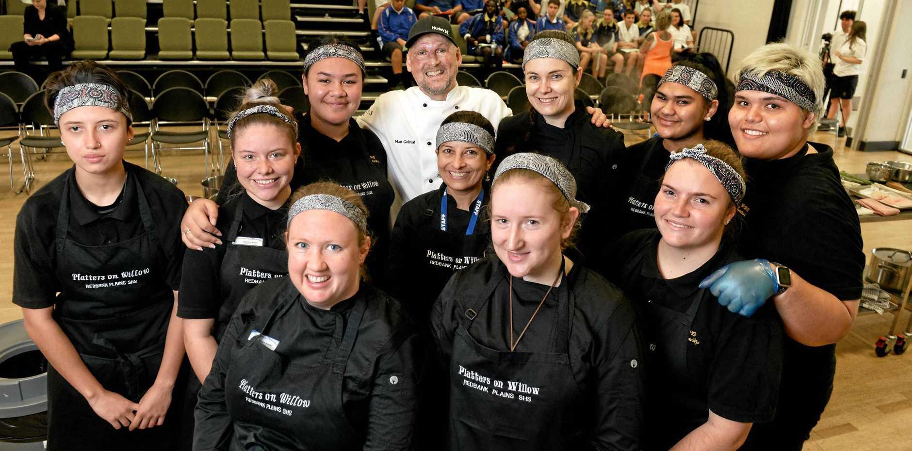 Celebrity chef Matt Golinski (back) put on a cooking demonstration at Redbank Plains State High School on Thursday.