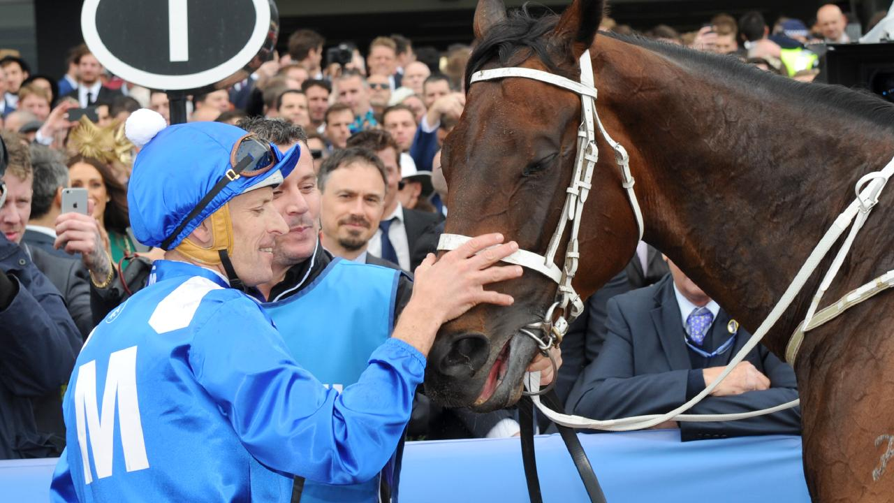 Hugh Bowman gives Winx a pat after winning the 2016 Cox Plate. Picture: Getty Images