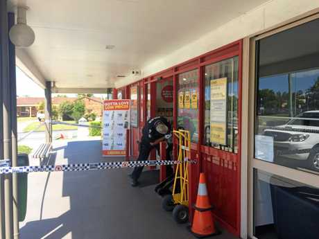 A scenes of crime officer dusts for prints at the Aroona Liquorland bottle shop after an October 1 robbery.