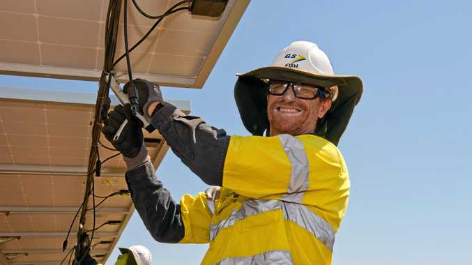 WIRE UP: Electrician Martin Fisher wires up solar array panels at Adani Renewables Australia's Rugby Run solar farm.