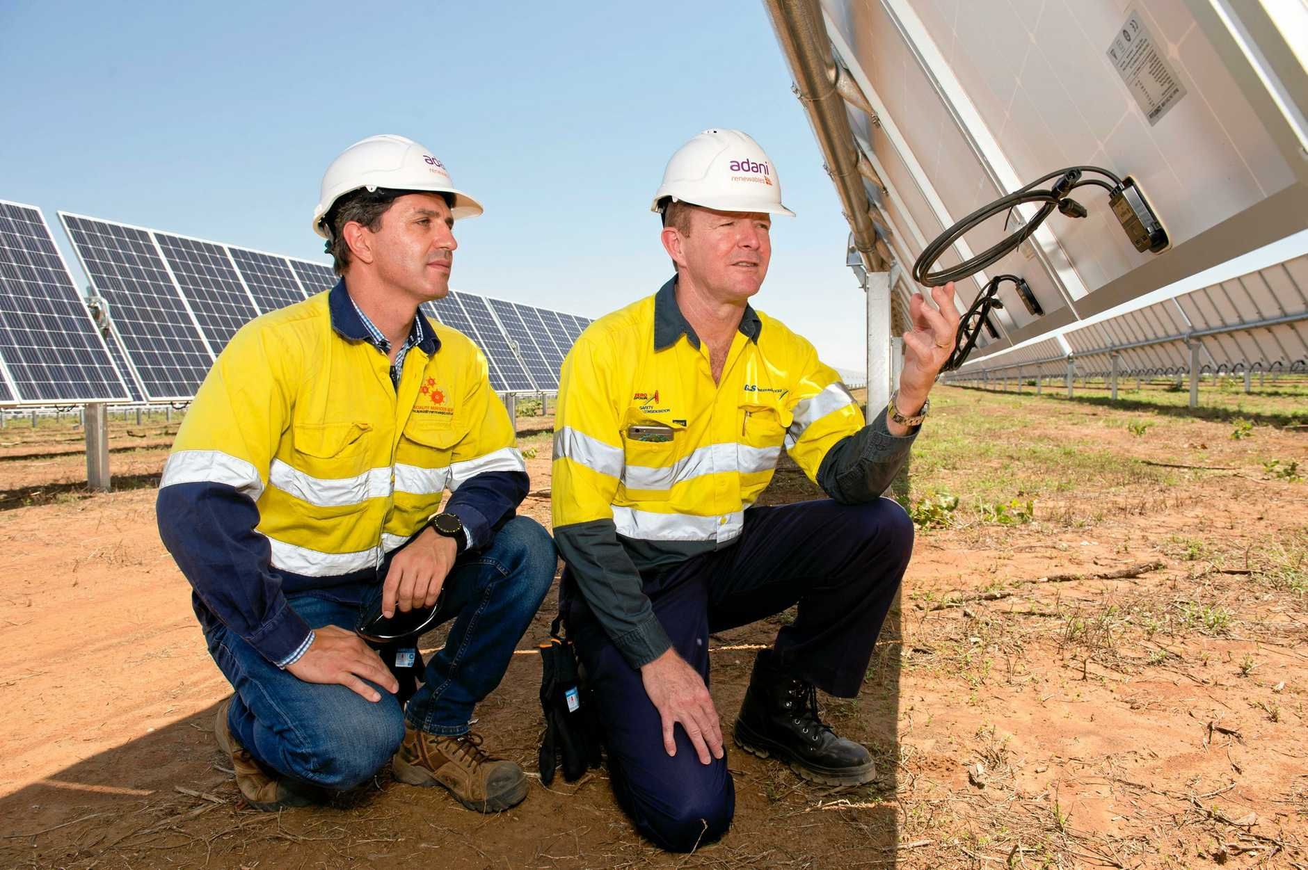 Mick Crowe (right), managing director of G&S Engineering, inspects the wiring on the back of a solar panel with Ricardo Brotto, project engineer for Speciality Services, at the Adani Renewables Australia's Rugby Run solar farm.