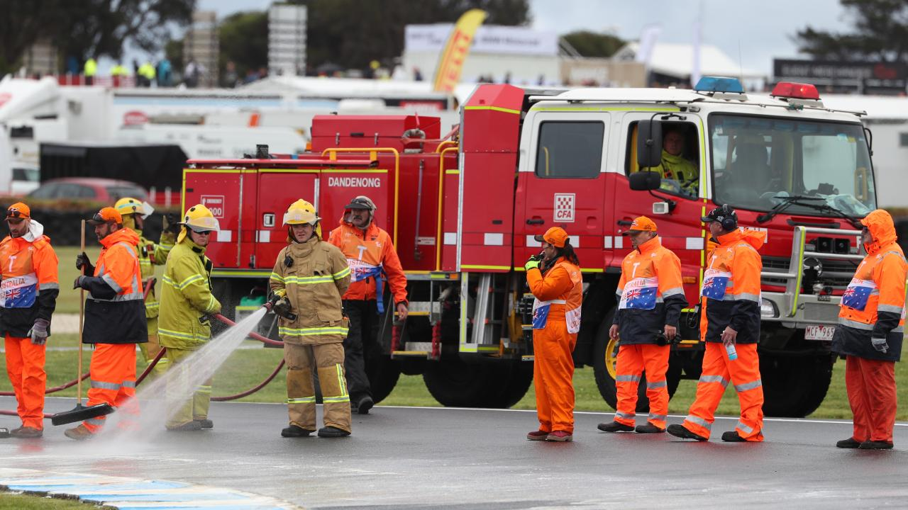 Workers clear oil from the track at the Australian Motorcycle Grand Prix 2018 on Phillip Island. Picture: David Crosling/AAP