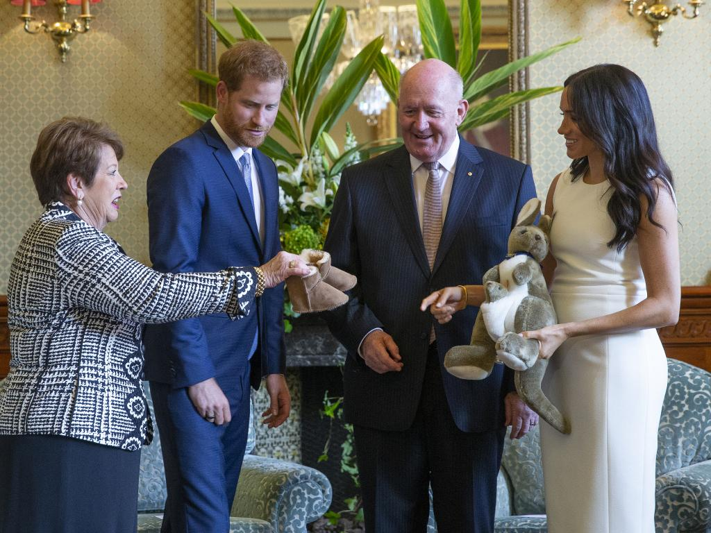 Governor-General Sir Peter Cosgrove and his wife Lady Lynne Cosgrove present a toy kangaroo and a pair of small Ugg boots to Harry and Meghan.
