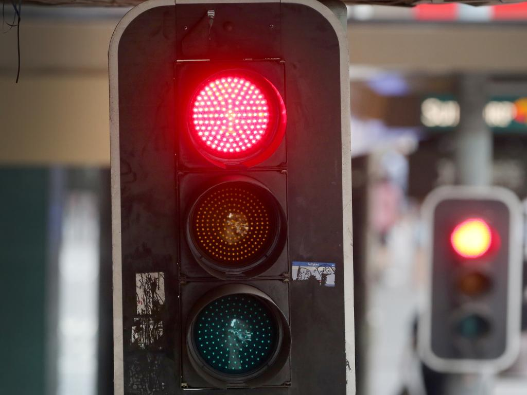 Different states have different rules about if it is OK to go through a red light to make room for an emergency vehicle. Picture: Jono Searle/AAP