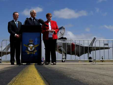 Defence Industry Minister Christopher Pyne, former prime minister Malcolm Turnbull and Defence Minister Marise Payne smile and nod in front of an F-35 jet. Picture: Tracey Nearmy