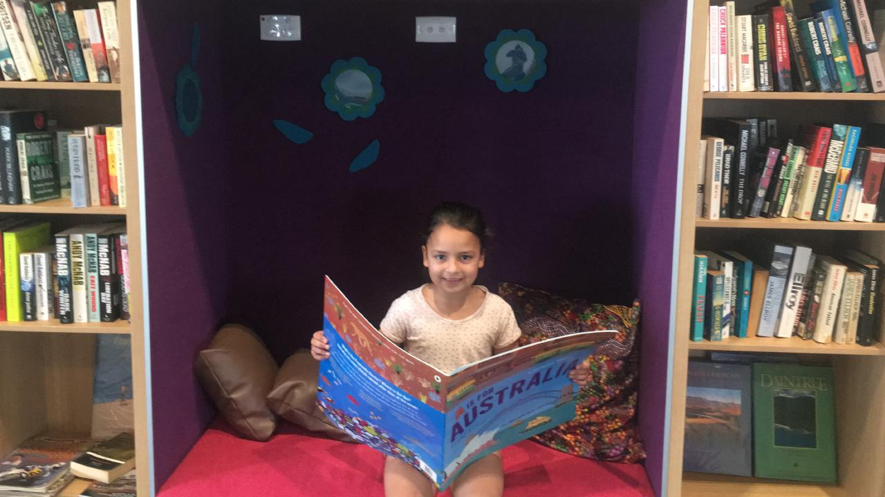 Leilani Hockney reads a book at the Family and Community Place Yarrabilba.