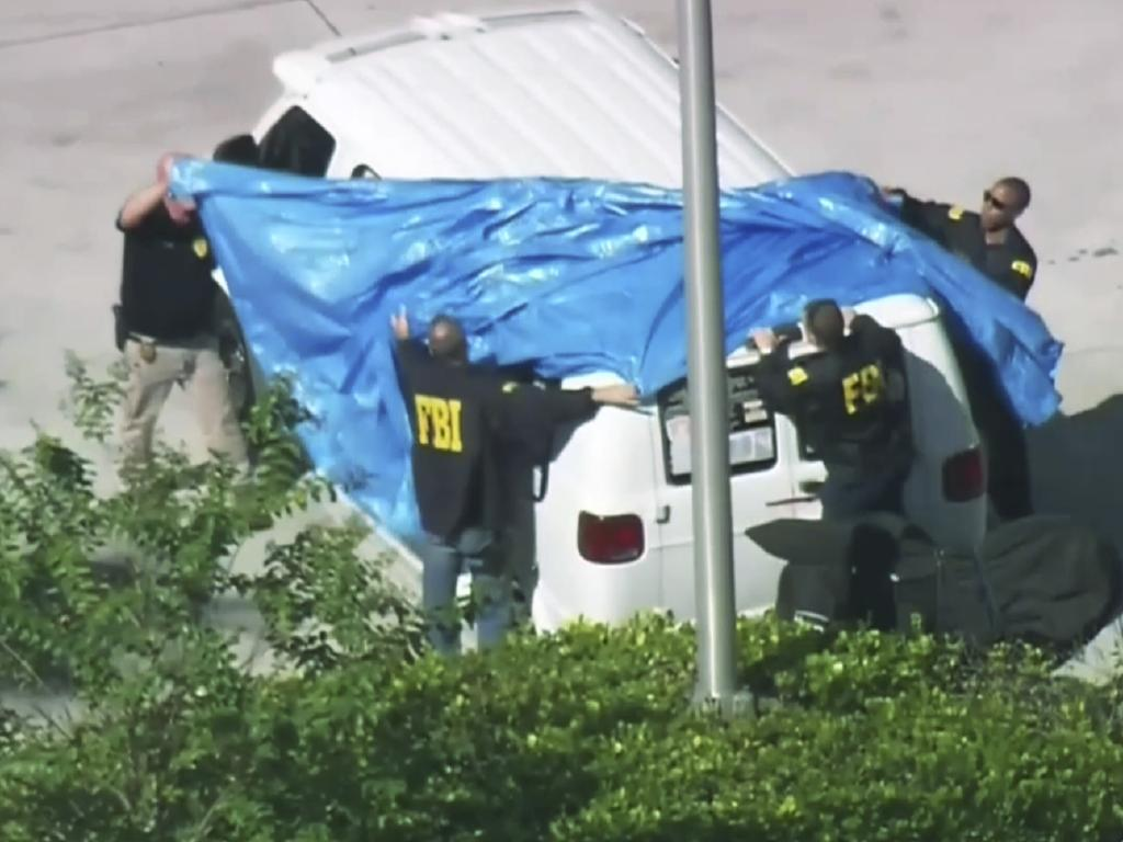 FBI agents cover a van parked in Plantation, Florida.  Picture:  AP