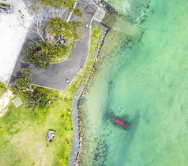 Mitch East shot this aerial view over Red Rock where a Landcruiser and a boat and trailer rolled into the water early Saturday morning.