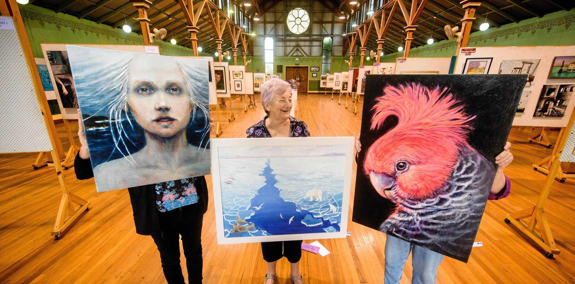 GOLDEN YEAR: Grafton Art Club president Averill Wiblen receives assistance to hang exhibition artworks.