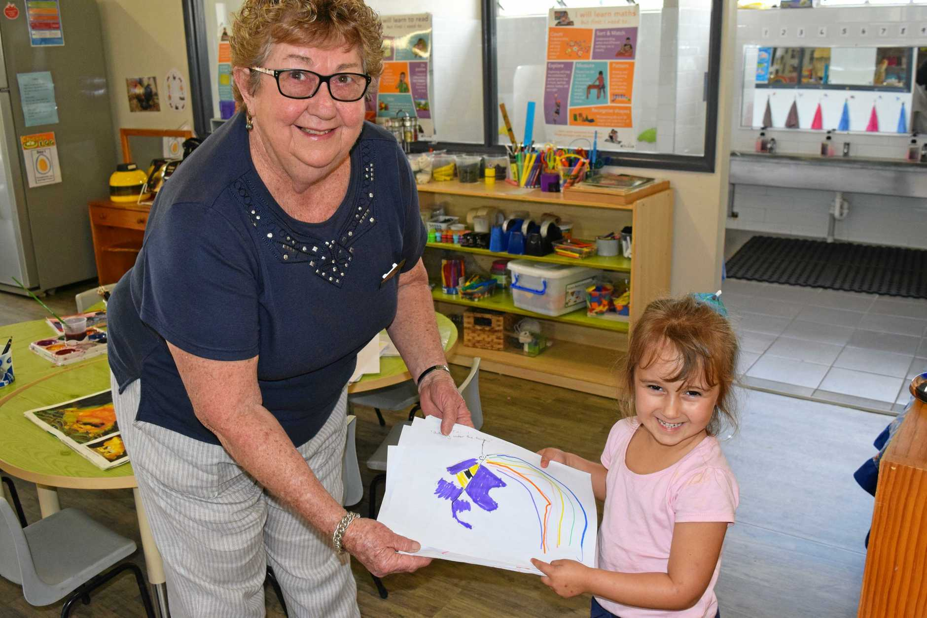 Four-year-old Bonnie Toohey-Peters hands over the Tinana Preschool and Kindergarten entries for the CraftFest placemat competition to Maryborough Artisan Lesley Mason.
