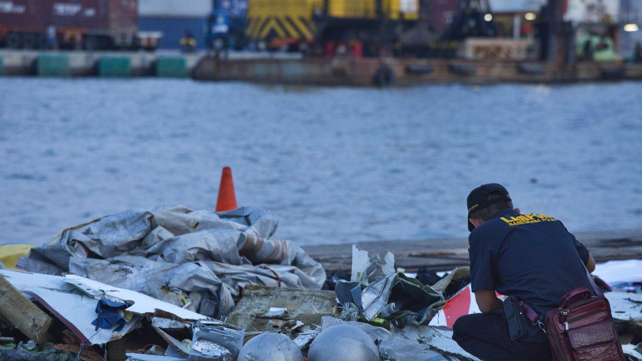 A forensic investigator looks through the remains of Lion Air flight JT 610 at the Tanjung Priok port on October 29, 2018 in Jakarta, Indonesia. Picture: Ed Wray/Getty Images