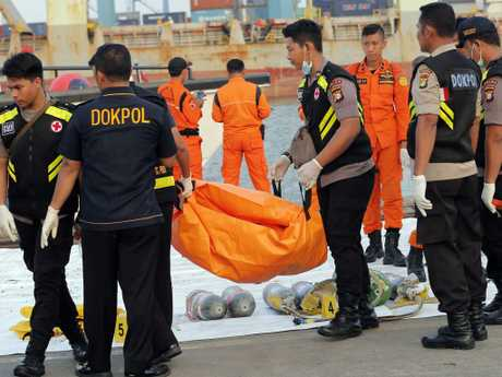 Police officers carry a body bag containing the remains recovered from the area where a Lion Air passenger jet crashed, at Tanjung Priok Port in Jakarta. Picture: AP/Tatan Syuflana
