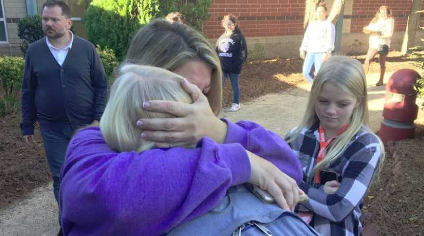 A terrified parent is reunited with her child after a student was shot dead at a North Carolina high school. Picture: Twitter