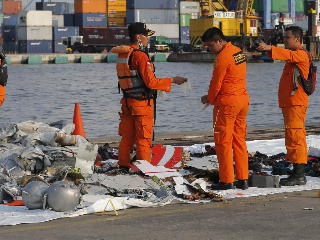 Indonesian Search and Rescue Agency crew inspect debris recovered from waters near the crash. Picture: AP/Tatan Syuflana