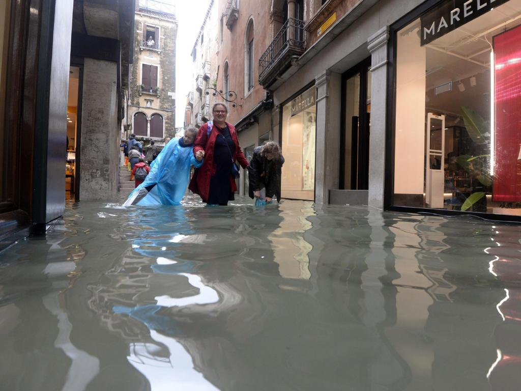 People walk in a flooded street of Venice, Italy, as 70 per cent of the lagoon city has been flooded by waters rising 149 centimetres above sea level. Picture: Andrea Merola/ANSA via AP