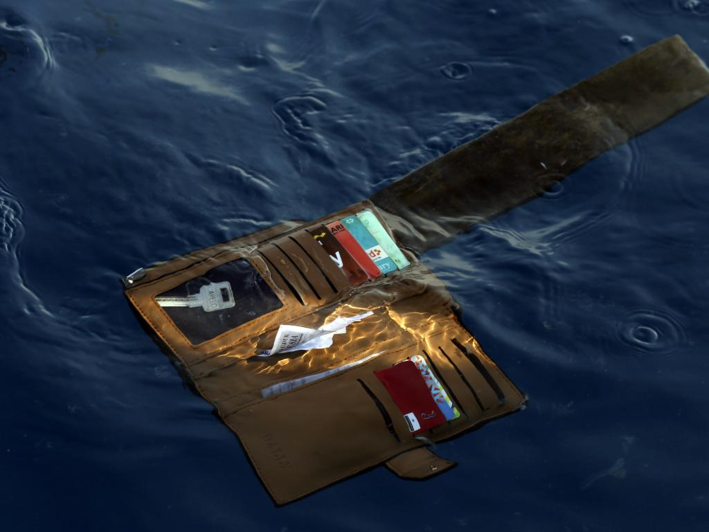 A wallet belonging to a victim floats to the surface. Picture: Achmad Ibrahim/AP