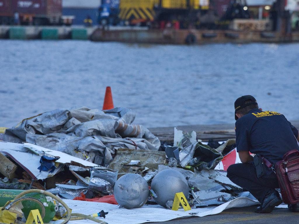 A forensic investigator looks through the remains of the doomed flight. Picture: Ed Wray/Getty Images