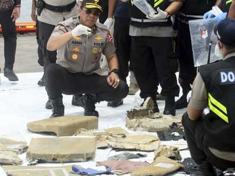 Indonesian forensic team members examine parts of a plane recovered from the area where a Lion Air plane is suspected to have crashed.