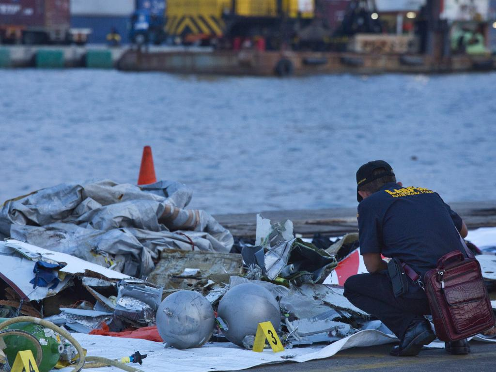 A forensic investigator looks through the remains of the plane. Picture: Ed Wray/Getty