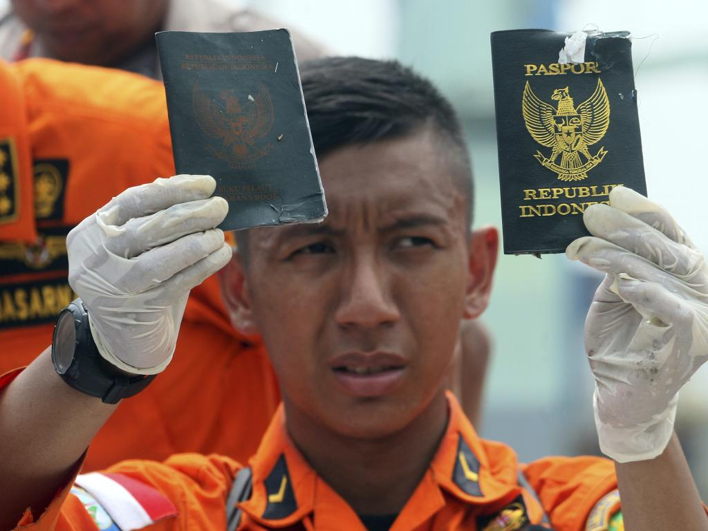 A rescuer shows passports recovered from the area where a Lion Air plane is suspected to crash, at Tanjung Priok Port in Jakarta, Indonesia, Tuesday, Oct. 30, 2018. Search and rescue personnel worked through the night to find victims of the Lion Air plane crash in Indonesia. (AP Photo/Binsar Bakkara)
