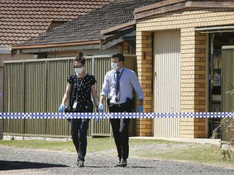 Detectives emerge from the side gate of a house at Red Cliffs. Picture: David Caird