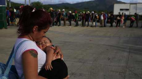 A woman carries her infant as migrants line up for rides in a handful of buses helping transport families with young children to the next stop, in Niltepec, southern Mexico. Picture: Rebecca Blackwell/AP
