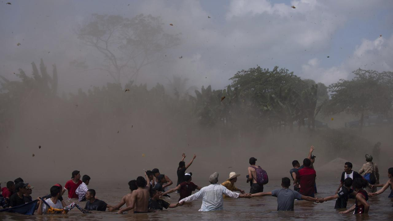 A helicopter creates dust clouds to discourage people from trying to cross the Suchiate River between Guatemala and Mexico. Picture: Santiago Billy/AP